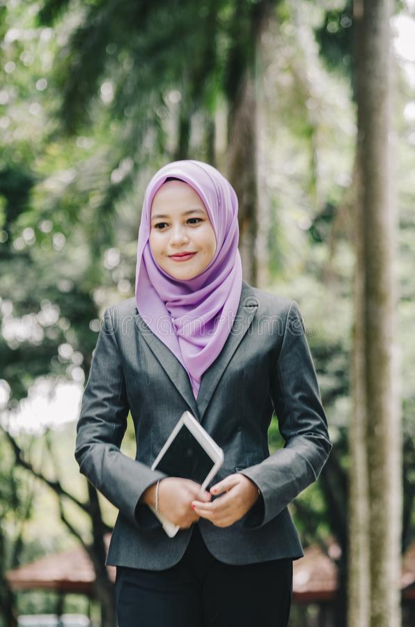 Portrait of smilling young professional muslimah businesswoman holding a tablet royalty free stock photography
