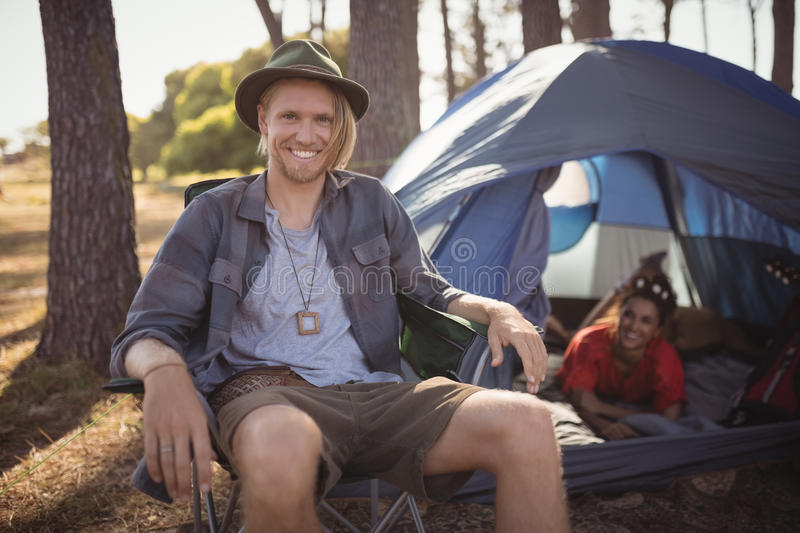 Portrait of smling man sitting on chair by tent stock photos