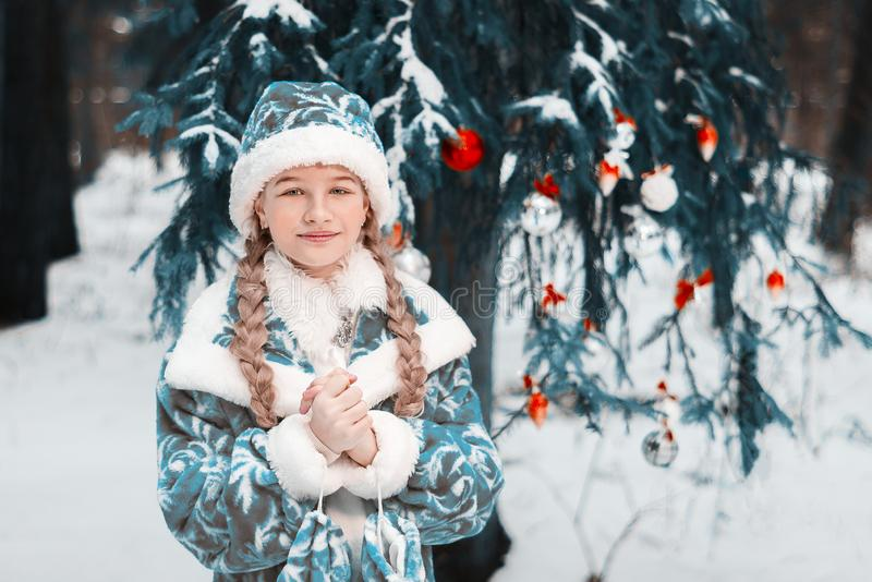 Portrait Snow Maiden. little girl froze in the winter in the forest. the child warms his hands. happy New Year. toned royalty free stock images