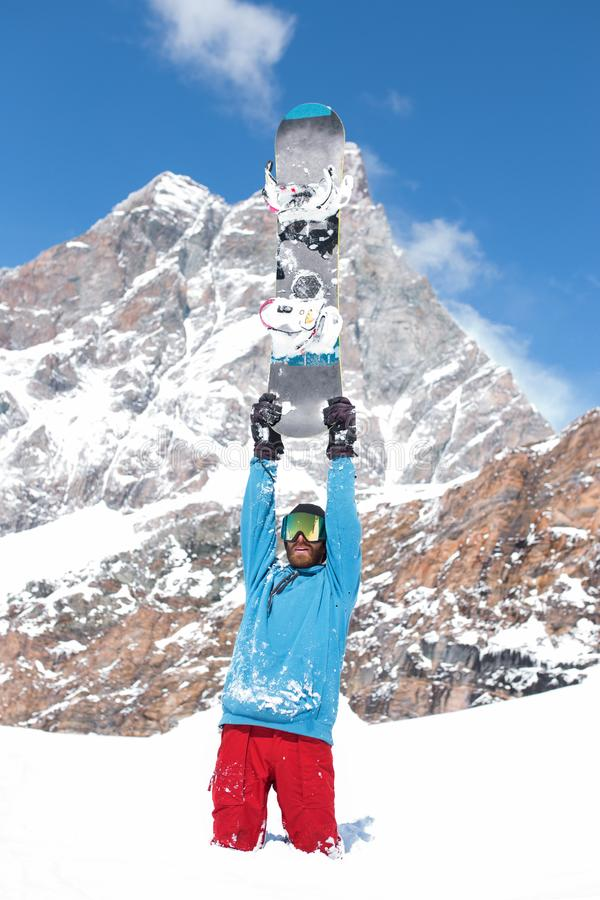Snowboarder in blue and red, raised hands arms up hold snowboard on top of hill, snow mountains snowboarding on slopes. stock photo