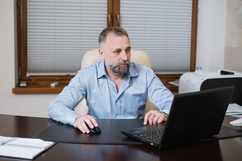 Portrait of solid middle age businessman working on laptop. Portrait of solid businessman Director of the organization in his office royalty free stock images