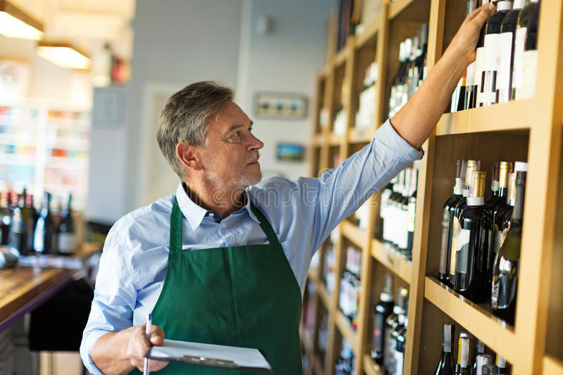 Portrait of sommelier taking inventory in wine store royalty free stock photo