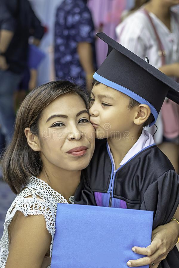 Portrait son graduated from kindergarten kissing mother royalty free stock photo