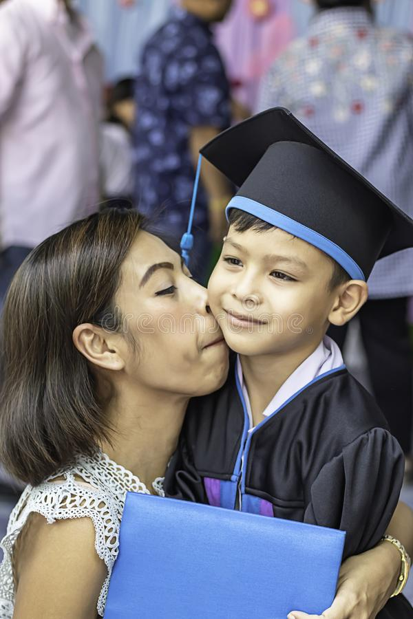 Portrait son graduated from kindergarten and mother kissing royalty free stock photo