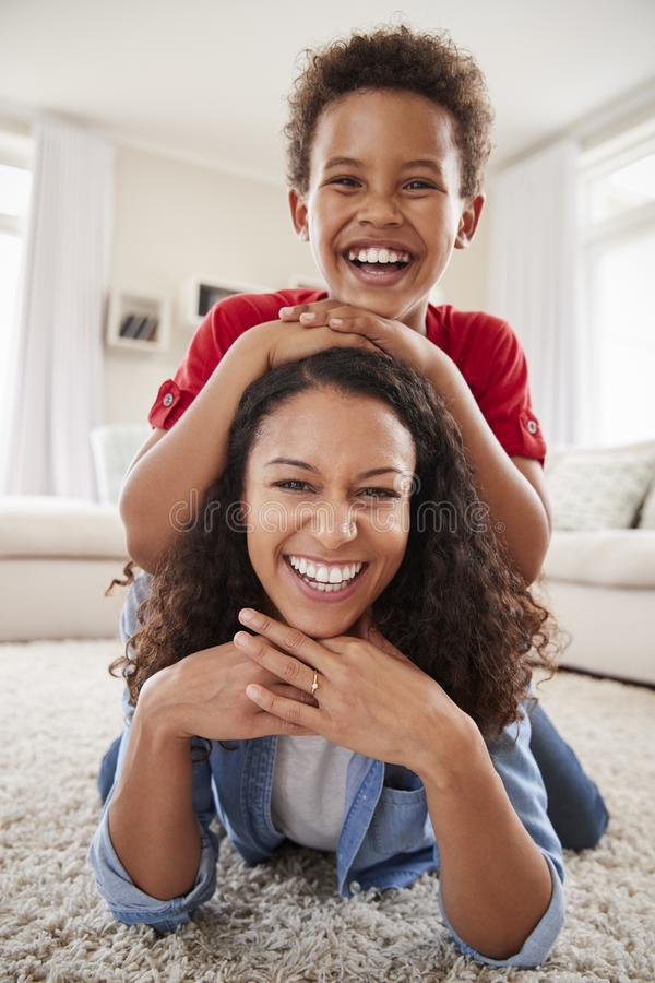 Portrait Of Son Lying On Mothers Back In Lounge royalty free stock photo