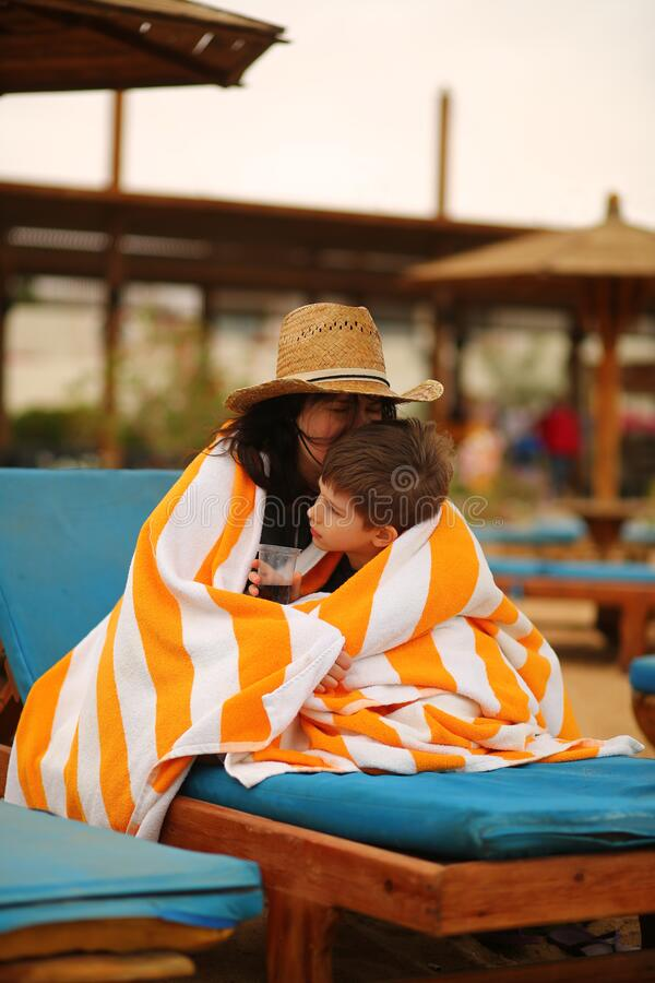 Portrait of a son and mother cuddling under towel on the cold beach sun bed. Portrait of a son and mother cuddling under towel on the cold beach sunbed royalty free stock images