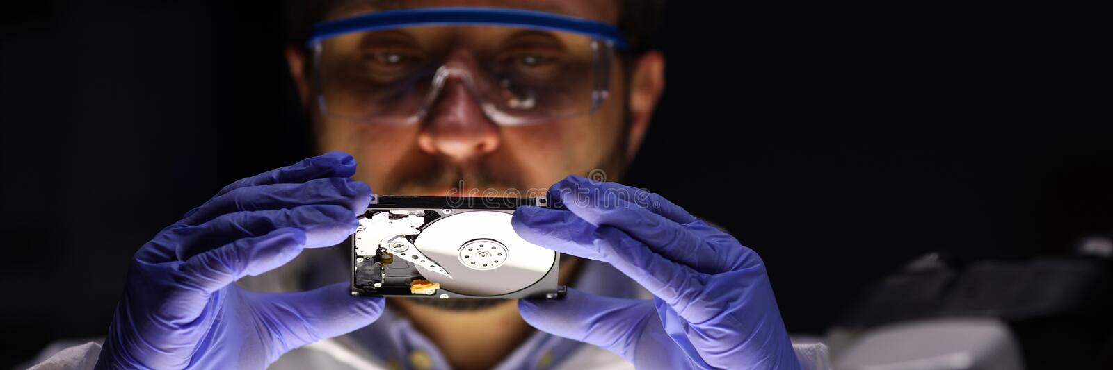 Computer master holding hdd. Portrait of specialist in eyewear looking at rigid disc. Man examining pc detail. Worker checking detail condition. Small hard disk stock photos