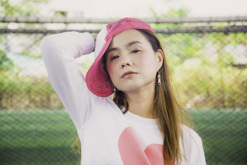 Portrait sport Asian woman in pink and white sportswear and wearing a hat, standing indoor football field with Sexy and cheerful stock images