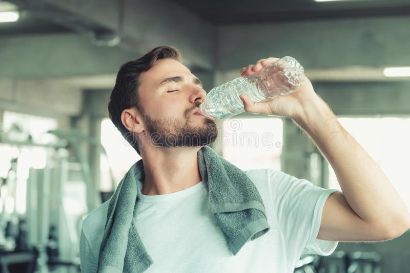 Portrait of Sport Man in Fitness Club and Drinking a Bottle of Water After Braking Exercised on Bodybuilding Equipment Background stock photos