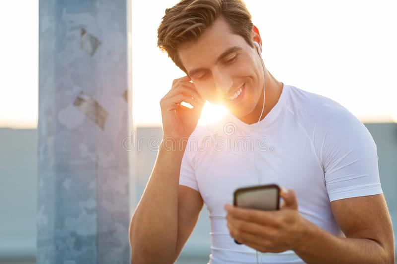 Sportive young man in the city with smartphone stock images