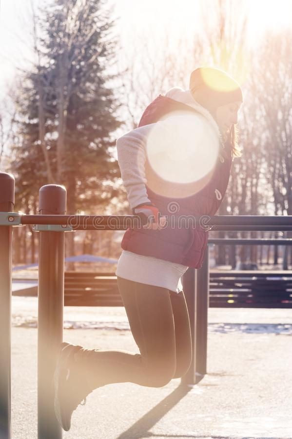 Portrait of a sports girl doing workout in the winter on an outdoor sports field. Exercises on Uneven Bars.  stock photography