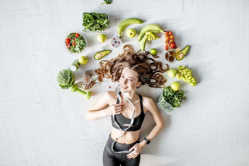 Portrait of a sports woman with healthy food. Beauty portrait of a sports woman surrounded by various healthy food lying on the floor. Healthy eating and sports stock images