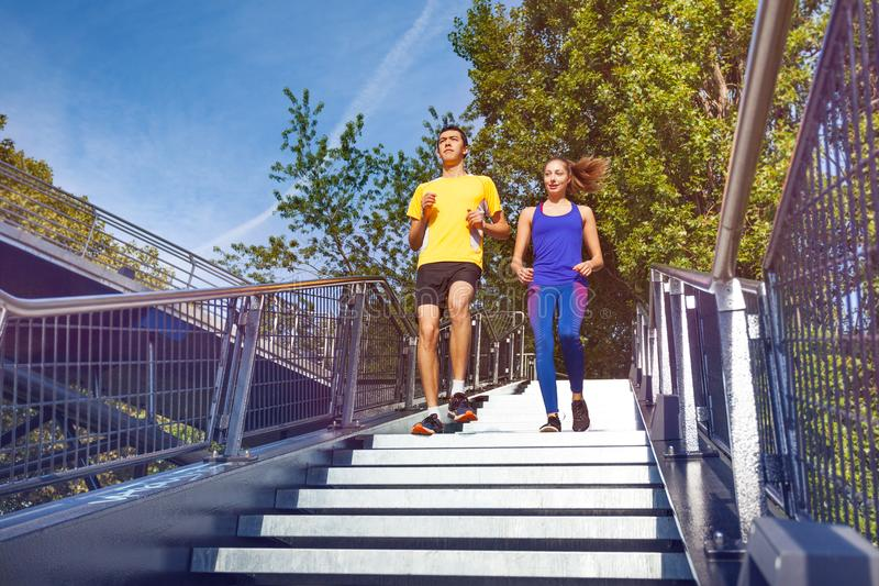Sporty couple running downstairs on city stairs stock photography
