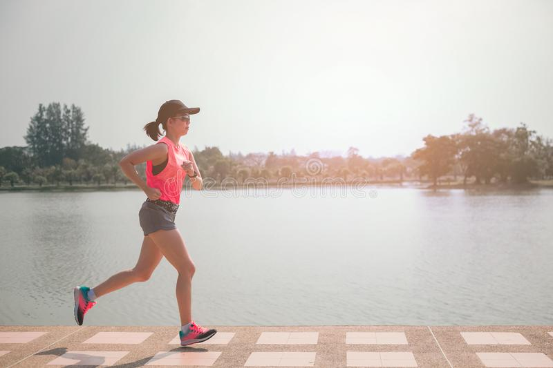 Portrait of Sporty female jogger morning exercise in the park.  stock photo