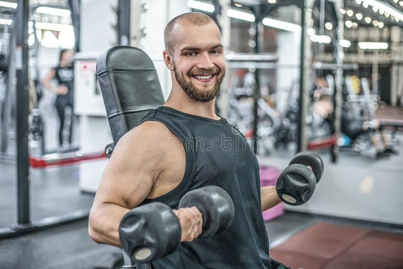 Portrait of sporty healthy strong muscle charismatic happy smiling handsome man bodybuilder hard training workout in well-equipped stock photos