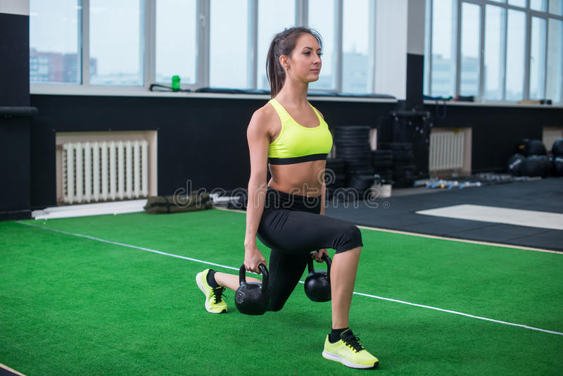 Portrait of a sporty woman doing lunges with dumbbells, working out legs muscles royalty free stock photo
