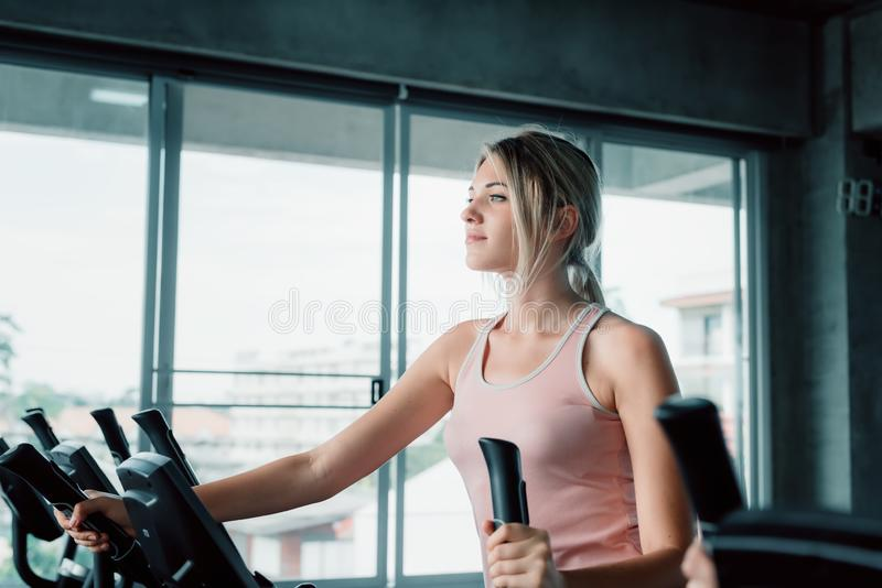 Sporty Woman Exercising Workout on Elliptical in Fitness Training Club., Pretty of Caucasian Women in Sportswear Working Out Cardi. O Training at Gym.,Wellness royalty free stock photos
