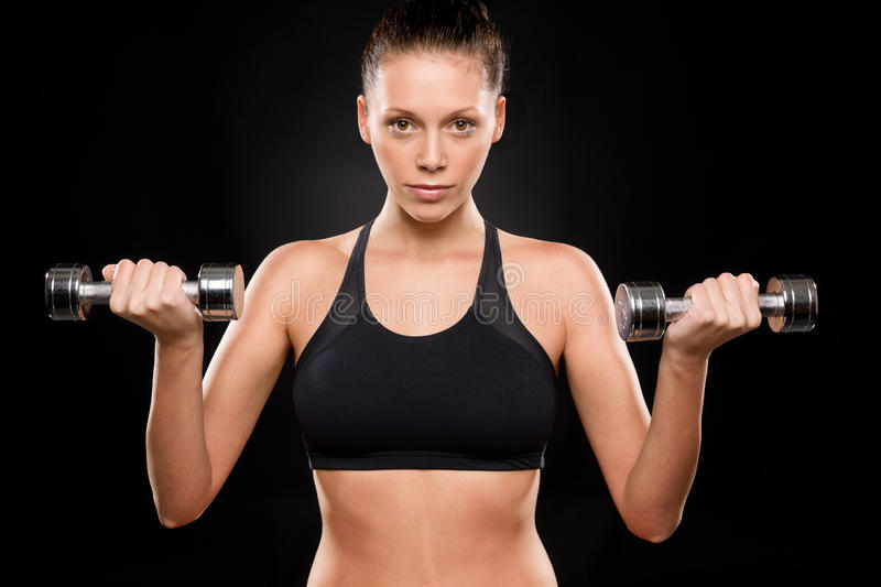 Portrait of a sporty woman lifting weights. With both hands royalty free stock photos