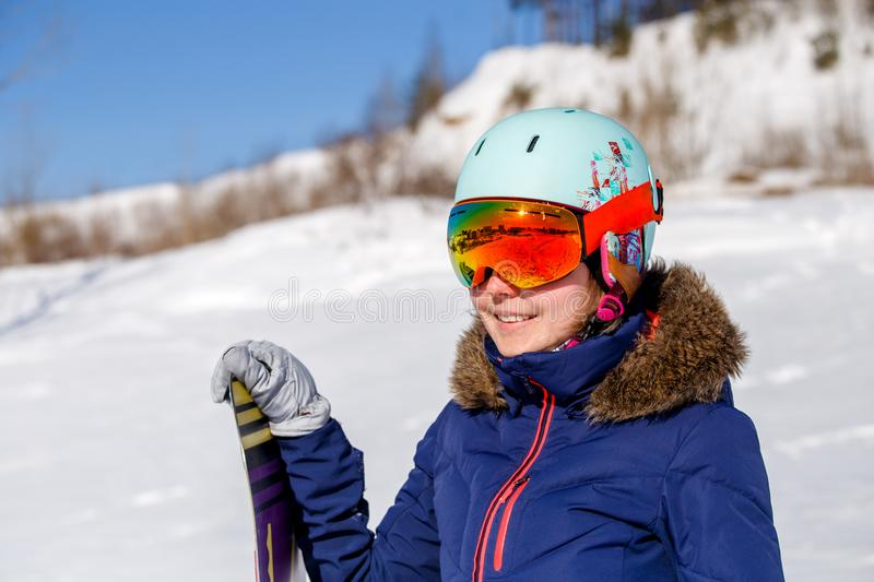 Portrait of sporty woman wearing helmet with snowboard looking at camera. On winter day royalty free stock photography