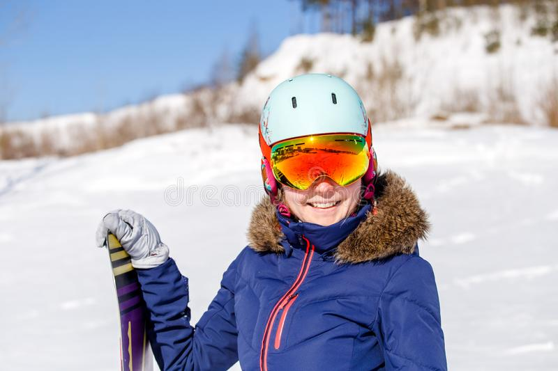 Portrait of sporty woman wearing helmet with snowboard looking at camera. On winter day stock photos
