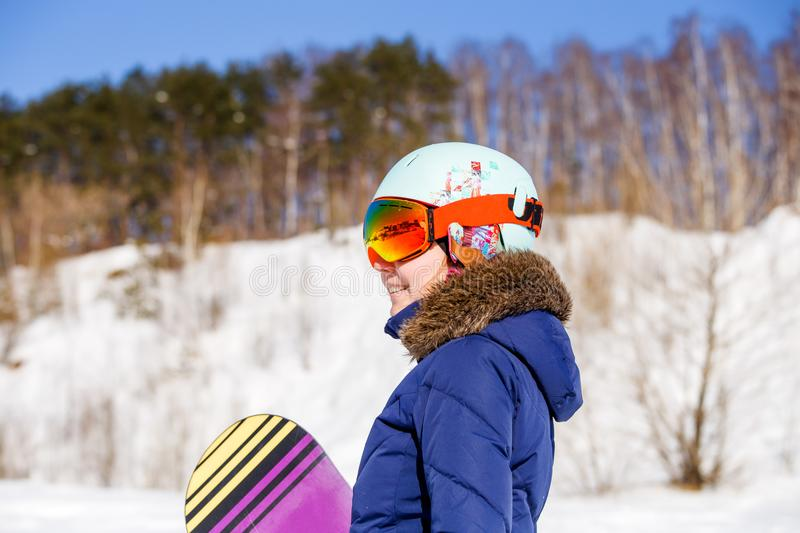 Portrait of sporty woman wearing helmet with snowboard. In winter stock photos