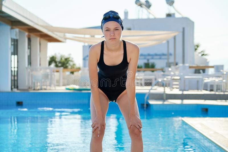 Portrait of girl in swimsuit with goggles swimming cap, outdoor pool royalty free stock images