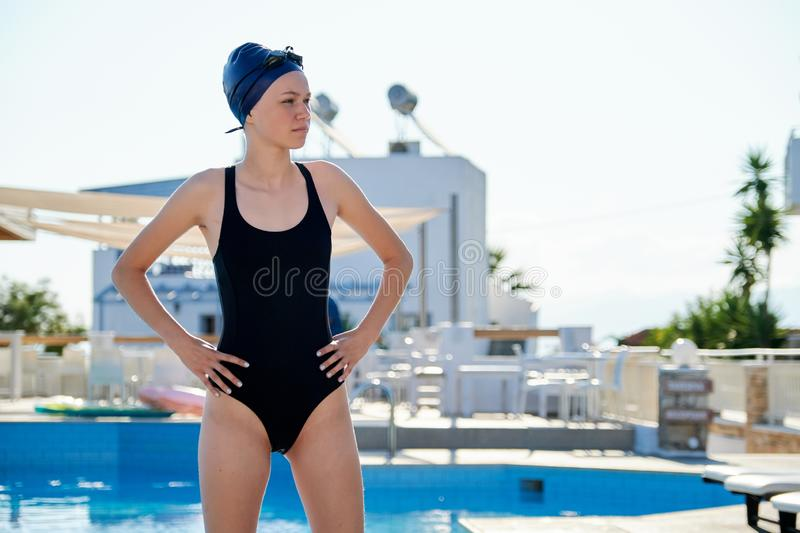 Portrait of girl in swimsuit with goggles swimming cap, outdoor pool royalty free stock photos