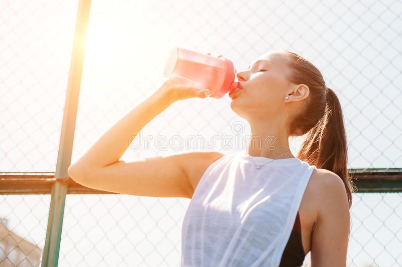 .Portrait of sporty young woman drinking cool water from bottle on summer sports field. Healthy lifestyle concept royalty free stock photos