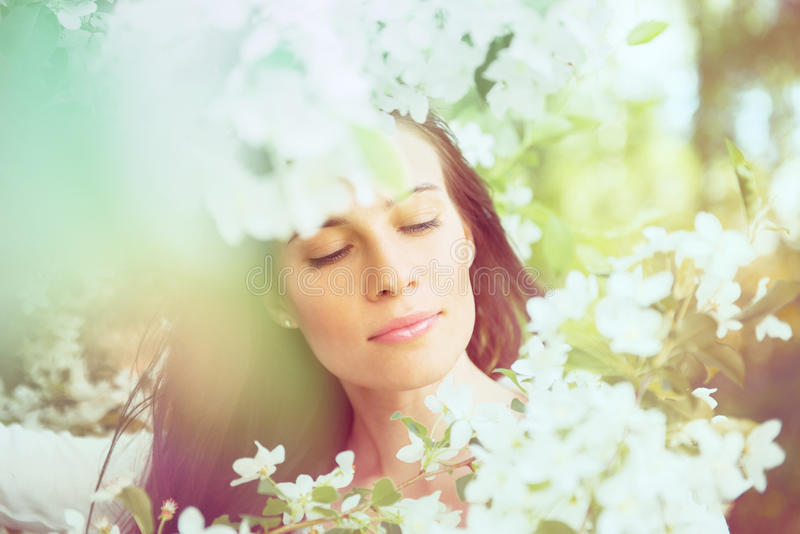 Portrait of spring brunette girl standing outdoor in blooming tr. Ees. Beautiful romantic woman in apple flowers. Young woman enjoying nature royalty free stock photography