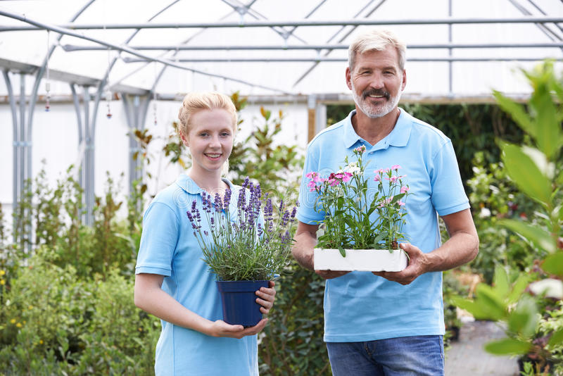 Portrait Of Staff At Garden Center Holding Plants stock image