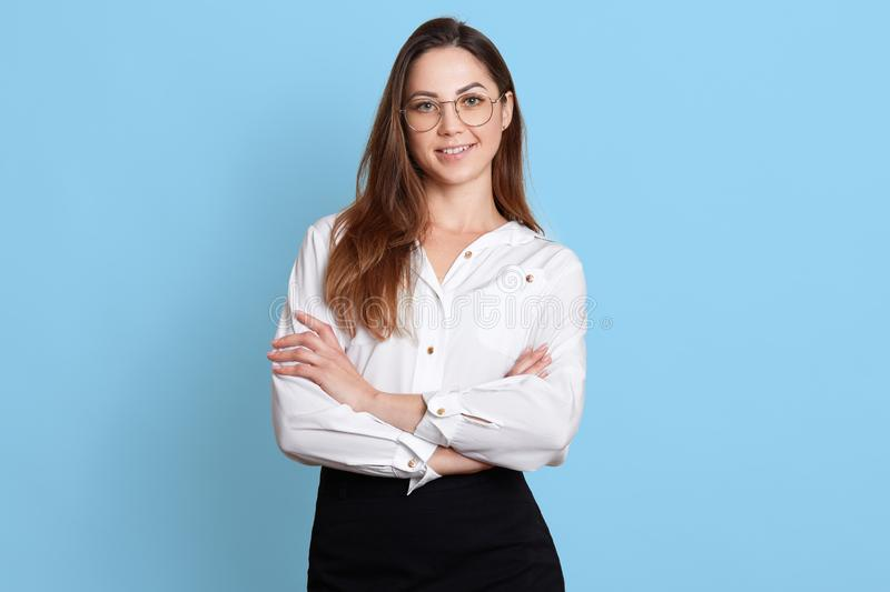 Portrait of standing cheerful businesswoman in fashionable eyeglasses, with folded arms, looking directly at camera, wearing white. Blouse and black skirt royalty free stock photo