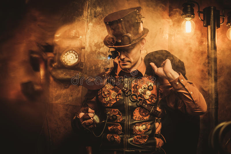 Portrait of steampunk man with various mechanical devices on vintage steampunk background.  stock photos