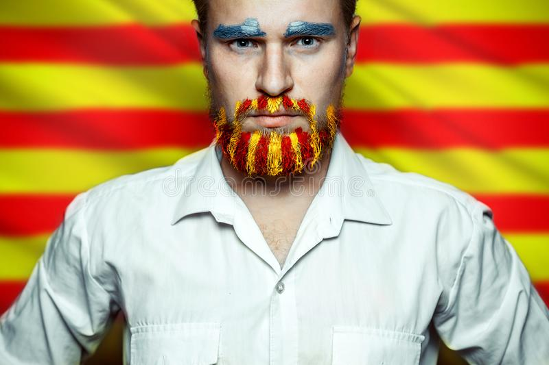 Portrait Of A Stern Man With A beard, Unraveled In Colors Of The Flag Of Catalonia. Referendum For The Separation Of Catalonia Fro royalty free stock photo