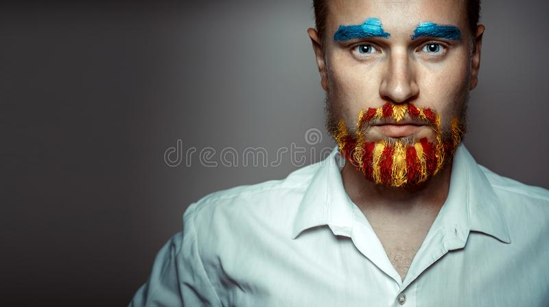 Portrait Of A Stern Man With A beard, Unraveled In Colors Of The Flag Of Catalonia. Creativity Portrait Concept royalty free stock photo