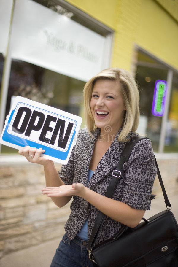 Portrait of store owner. A happy owner holding up an Open sign in front of her new business stock image