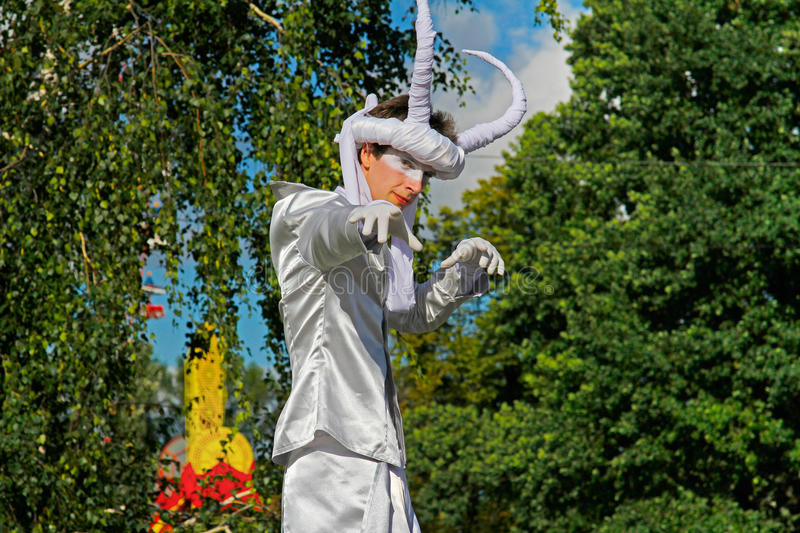 Portrait of street actor with horns on stilts at the festival `Inspiration` in VDNH park in Moscow royalty free stock image