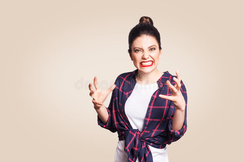 Portrait of stressed and annoyed young casual styled caucasian woman with hair bun holding hands in mad furious gesture, screaming royalty free stock photo