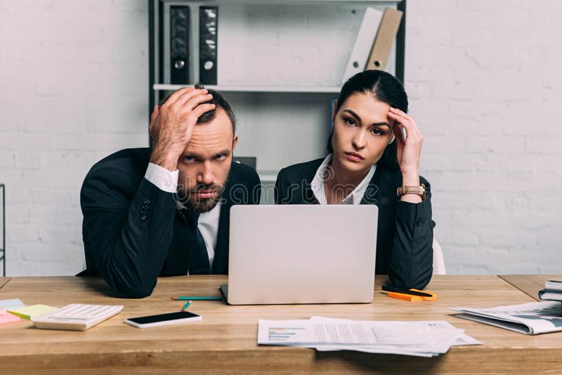 portrait of stressed business people at workplace with documents and laptop stock images