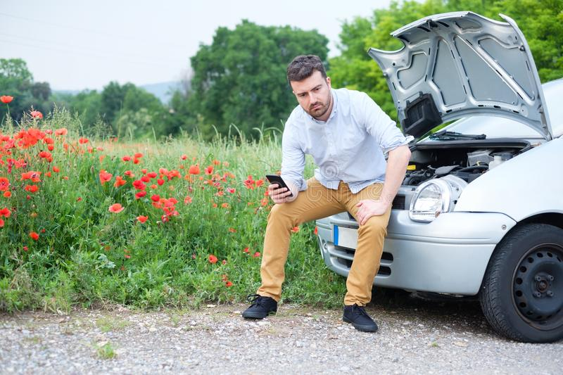 Portrait of stressed man calling on cellphone for service his breakdown car royalty free stock images