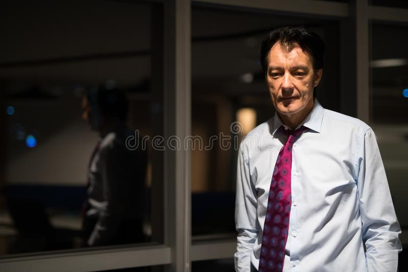 Portrait Of Stressed Mature Businessman In Office At Night stock images
