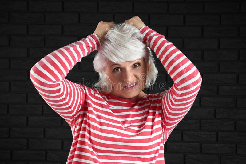 Portrait of stressed mature woman on dark background stock image