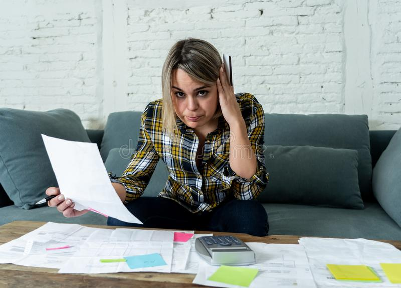 Portrait of stressed and overwhelmed young woman accounting home and business finances paying bills. Portrait of worried and desperate young woman in stress stock images