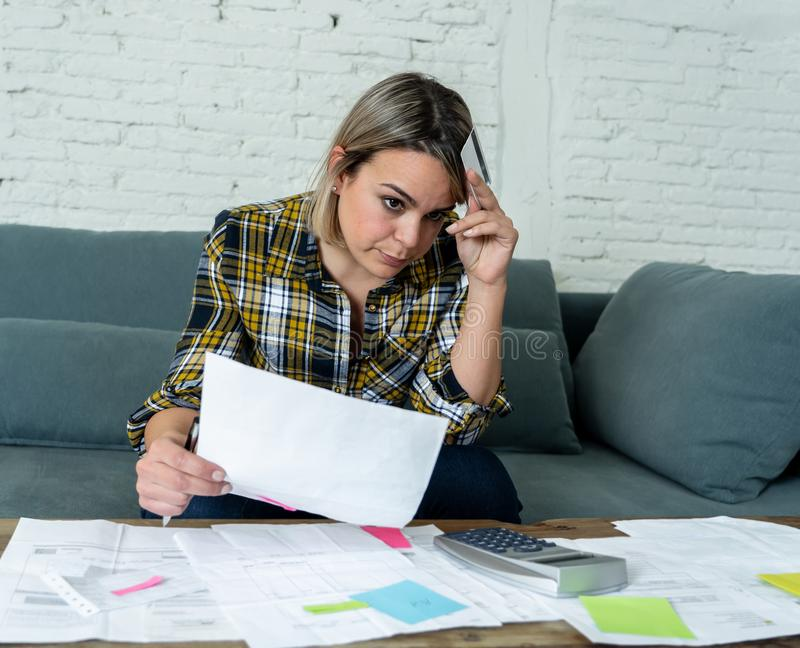 Portrait of stressed and overwhelmed young woman accounting home and business finances paying bills. Portrait of worried and desperate young woman in stress stock photo