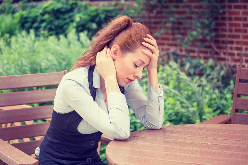 Portrait stressed sad young woman outdoors. Urban life style stress. Portrait stressed sad young woman sitting outdoors. City urban life style stress stock images