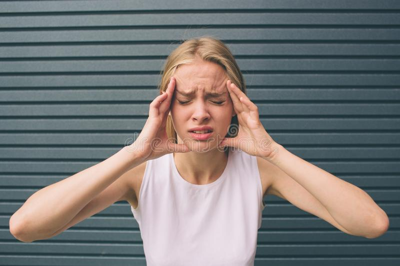 Portrait of a stressed woman holding head in hands. royalty free stock image