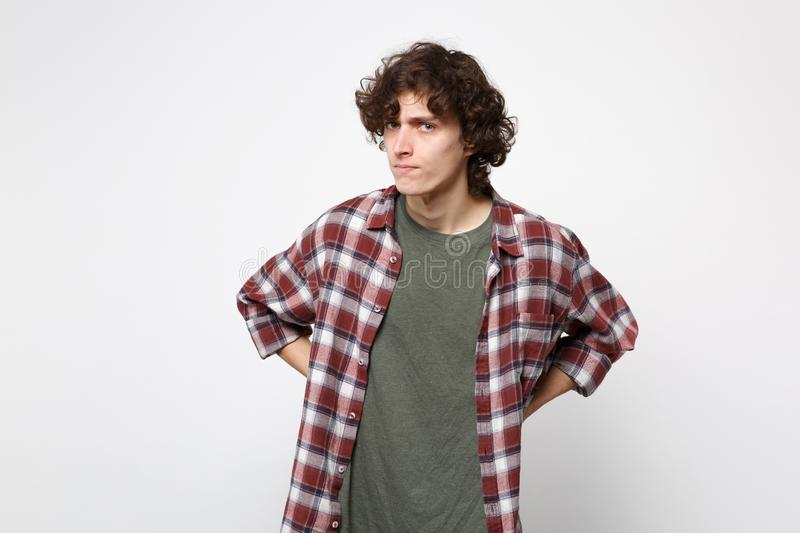Portrait of strict dissatisfied young man in casual clothes standing with arms akimbo on waist isolated on white royalty free stock images