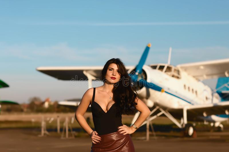 Portrait of a strong beautiful independent young woman in leather skirts near the ancient airplane. Fashion Lifestyle stock photos