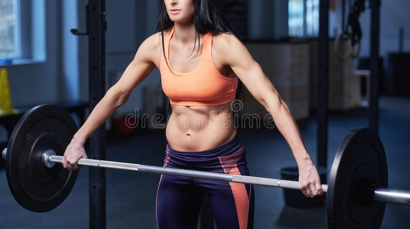 Portrait of a strong brunette sporty woman in a sportswear doing exercise with a barbell at the gym. stock photos