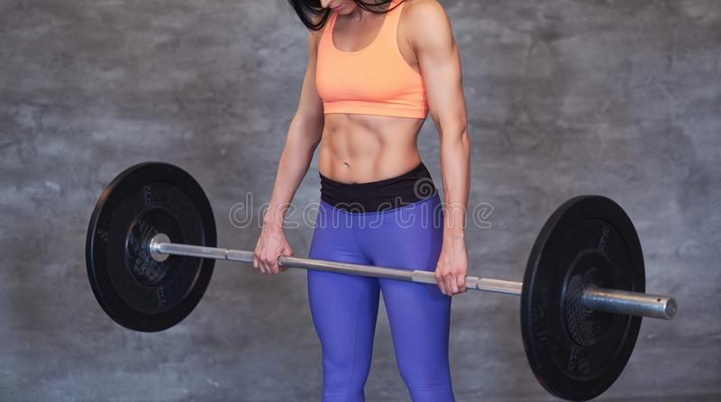 Portrait of a strong brunette sporty woman in a sportswear doing exercise with a barbell at the gym. stock photography