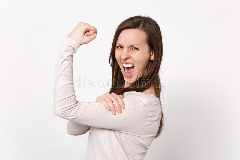 Portrait of strong crazy screaming young woman in light clothes showing biceps, muscles isolated on white wall royalty free stock photography